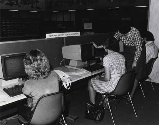 <p>Interior view: People are sitting in front of computers.  Behind the computers, on top of a partition, is a sign: Searching the book catalog by computer.  A librarian is helping a patron who is sitting at a computer station.  In the background is the card catalog.  A patron is using a shelf as a table while looking at a book.</p>
