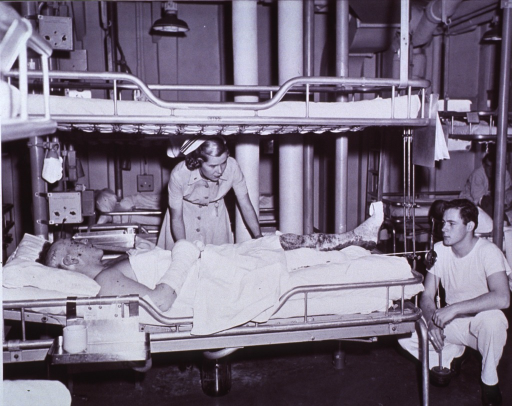 <p>Navy nurse (Lt. Jg. Woody) changes patient's position while corpsman adjusts weght on right stump.</p>