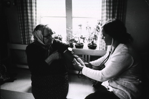 <p>A nurse is adjusting a sphygmometroscope (?) on the arm of an elderly woman.</p>