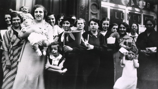 <p>Mother's Club members gathered in front of a building for a group photo with some of the children.</p>