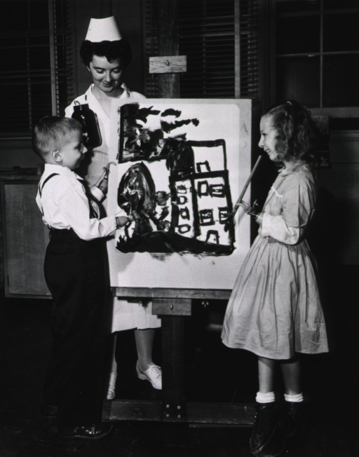 <p>A young boy and a young girl stand in front of an easel and paint in oils.  The two children have prosthetic arms.  A female therapist stands behind the easel next to the boy and holds a jar of paint.</p>