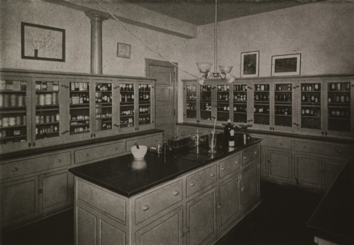 <p>Interior view: along the walls are cupboards containing bottles; a counter is in the middle of the room.  The pharmacy is located in the basement of the Main Building.</p>