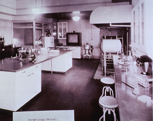 <p>Interior view: laboratory benches and tables, a large pressurized sterilizing unit, and such equipment as microscopes, Petri dishes, and racks of test tubes are shown.</p>
