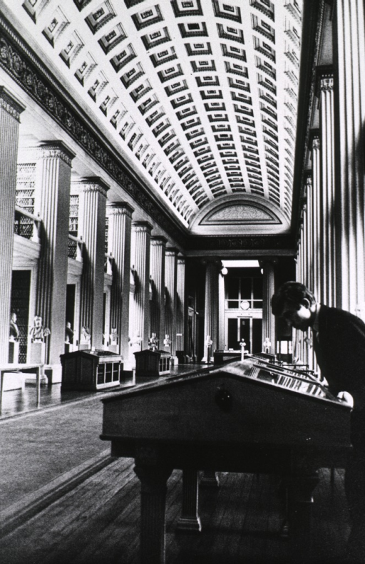 <p>Interior view: a student is standing at an exhibit case along the side of a large hall in the library.</p>