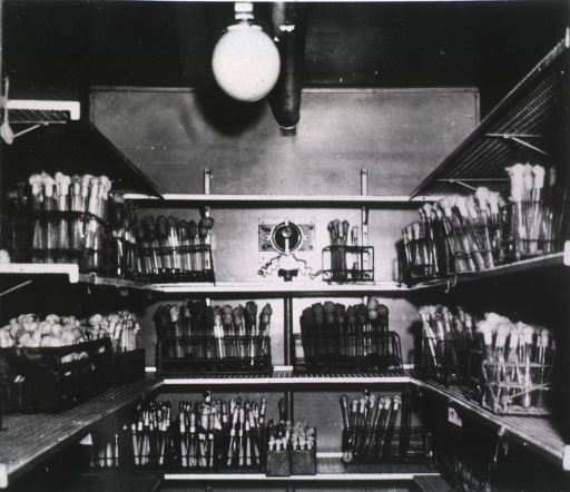 <p>Interior view: test tubes are on shelves; a large light fixture is hanging from the ceiling.</p>