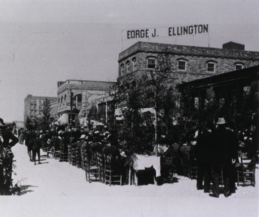 <p>Photograph of a luncheon held outdoors. Rows of men in bowler hats and suits and women in formal wear and hats are shown at long tables positioned on a street in San Francisco. Several buildings appear in the background, including one, with a sign &quot;[G]eorge J. Ellington&quot; on its roof.</p>