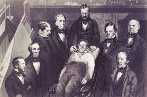 <p>Interior view: a physician is administering ether to a patient sitting back in a chair; several physicians are standing on both sides observing the procedure.</p>