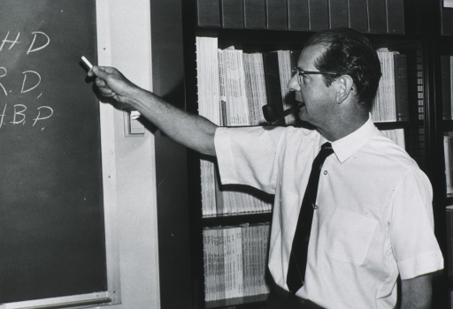 <p>Half length, left profile; wearing glasses, smoking pipe; standing beside bookcase, pointing to blackboard.</p>