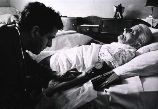 <p>A physician, at the bedside of an elderly woman, is checking her blood pressure.</p>