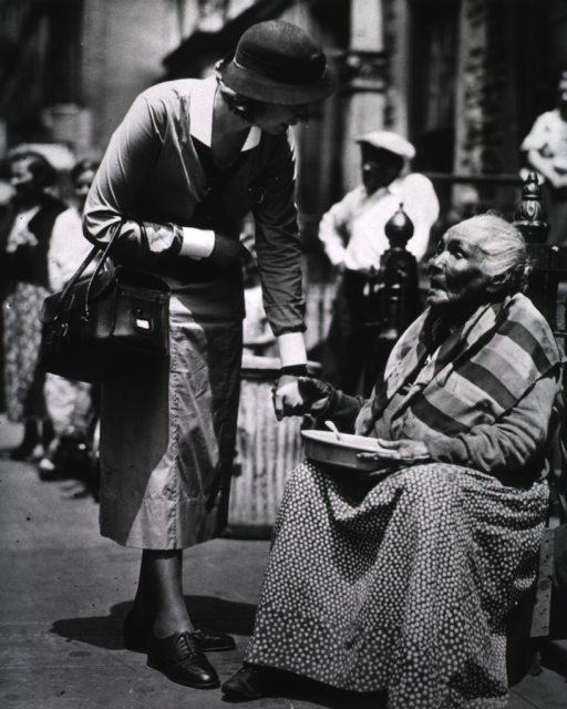 <p>View of a nurse stopping along the street to talk with an elderly woman who is sitting on the steps.</p>