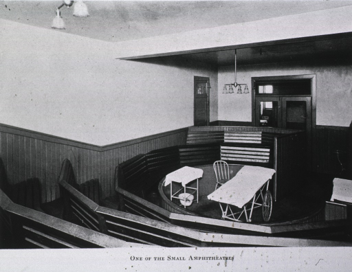 <p>Interior view: a small amphitheater located in the basement of the Main Building; in the pit are a wheeled table, a small stand, and a chair; wood wainscoting throughout.</p>