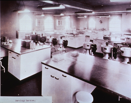<p>Interior view: laboratory tables, trays of test tubes, and several portable centrifuges are visible in a large room with several windows complemented by numerous overhead lights.</p>