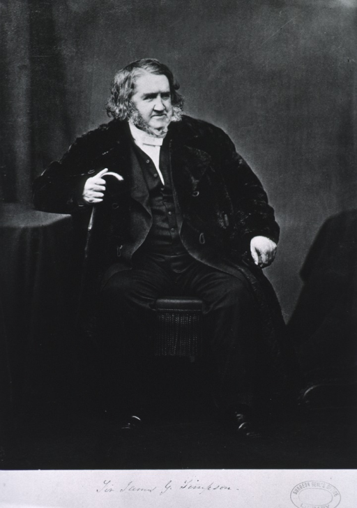 <p>Seated, full length, right pose; wearing fur coat; one hand holding cane.</p>