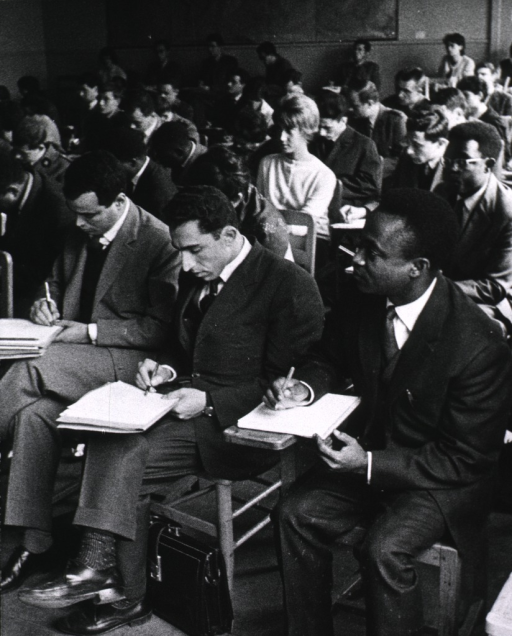 <p>Interior view: a large group of medical students are sitting in a classroom taking notes.</p>
