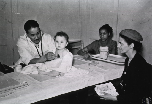 <p>View of an African American physician examining an infant while a nurse takes notes and the infant's mother looks on.</p>
