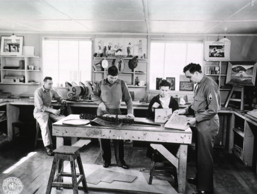 <p>Several patients and a serviceman in uniform shown working at various crafts.</p>
