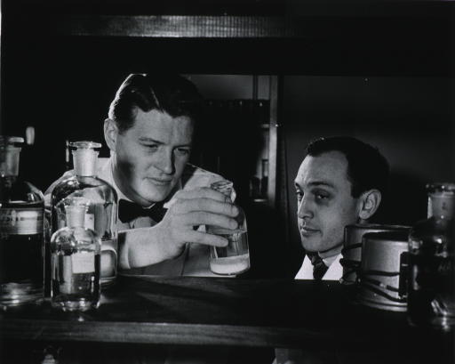 <p>Head and shoulders of Anfinsen and Steinberg; they are framed by a shelf on which are glass containers and other chemical apparatus.</p>