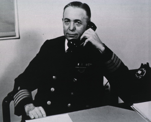 <p>Half length, seated at desk, telephone in hand, uniform.</p>