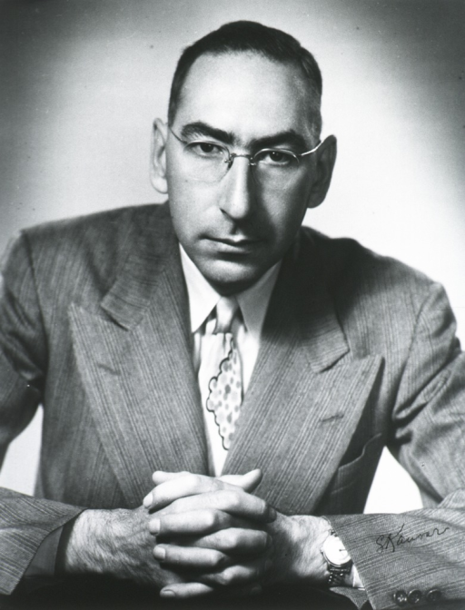 <p>Half-length, seated, full face; wearing glasses; hands together in front.</p>