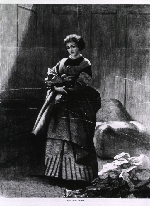 <p>The Red Cross [woman standing in a room, full length, with a band on her arm].</p>