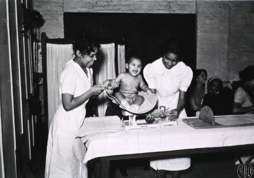 <p>A nurse weighs an infant while other children sit nearby.</p>