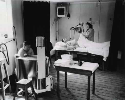 <p>Two male patients receive treatment under the supervision of a nurse.</p>