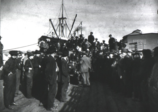 <p>Large group of men are standing on a dock listening to a man speak; a large ship is in the background.</p>