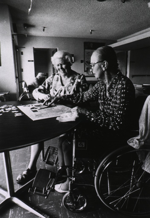 <p>Two elderly women, one in a wheelchair, sit at a table in a room in an (retirement facility?) recreation room. They are about to finish a jgsaw puzzle of a map of the United States.</p>