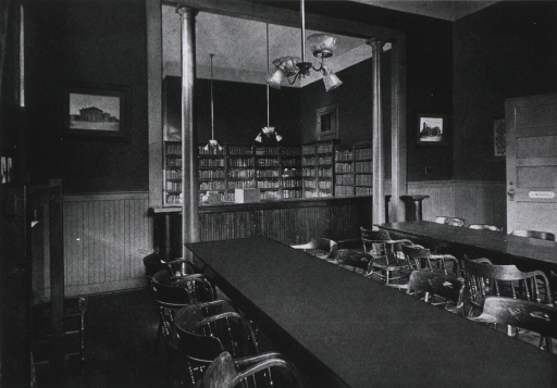 <p>Interior view: a wood wainscot reading room with chairs and two long tables; the book and periodical collection is in the background.  The library is located on the first floor of the Main Building.</p>