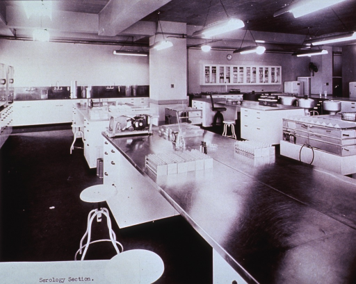 <p>Interior view: large room with several laboratory tables on which are trays of test tubes; other equipment, such as centrifuges, also visible.</p>