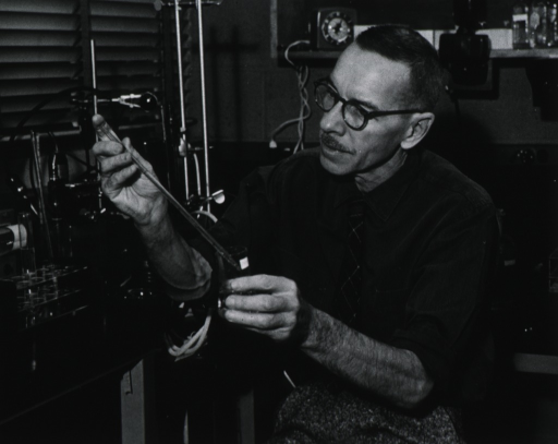 <p>Half-length, seated in laboratory, left pose; wearing glasses; holding pipette and beaker.</p>
