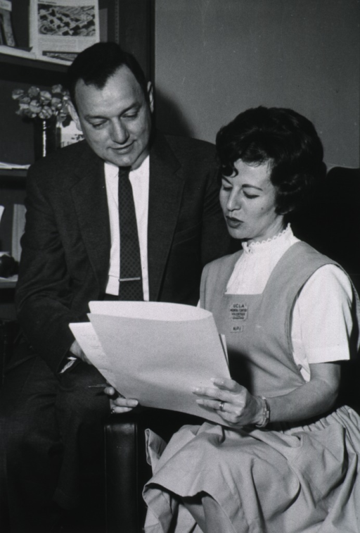 <p>Full length, full face (head downward); seated on arm of chair, reviewing papers with a hospital volunteer aid.</p>