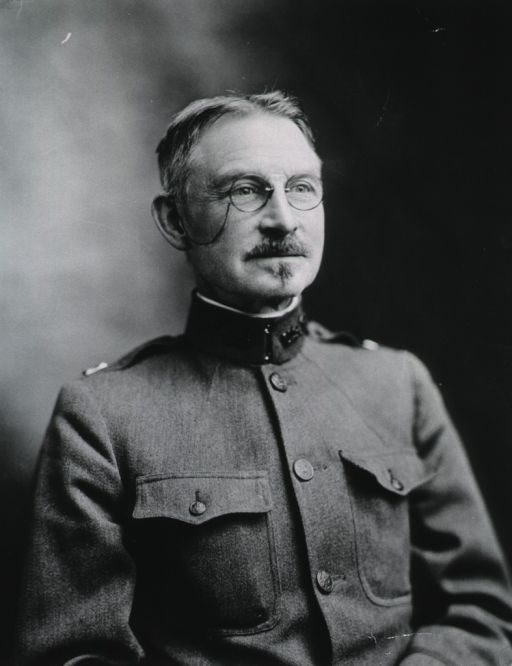 <p>Head and shoulders, front pose; in uniform.  Wearing glasses.</p>