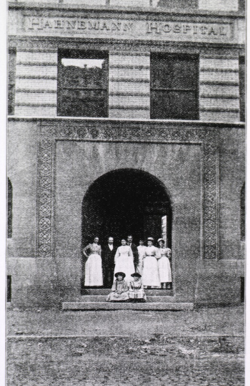 <p>Exterior view of the front entrance of the hospital with several nurses and two men standing at the entryway and two children sitting on the steps.</p>
