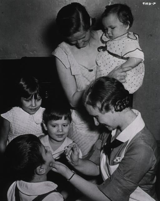 <p>A nurse checks the mouth of a child while the mother and three other children look-on.</p>