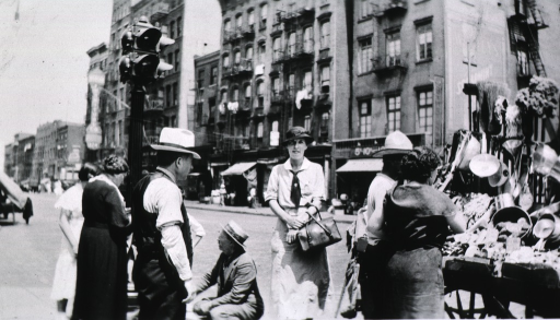 <p>Showing Miss Brown on Houston Street standing near a street peddler's cart.</p>