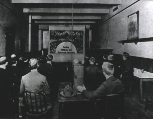 <p>View from behind the slide projector showing a room in which several men are seated watching a slide show.</p>