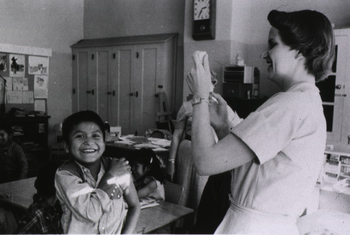 <p>A child smiles at the camera as he holds his exposed shoulder. A nurse stands in front of him and smiles as she handles the vaccination. Behind them in the classroom are other students and a teacher.</p>