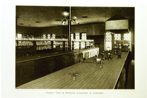 <p>Interior view: shelves with bottles are on top of a long counter with doors on the bottom; a lab table is in the foreground with what appear to be drawings of chemistry paraphernalia on top.</p>