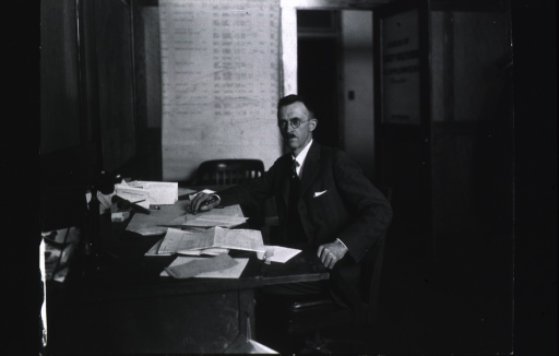 <p>3/4 length, full face, body to left, seated at desk.</p>