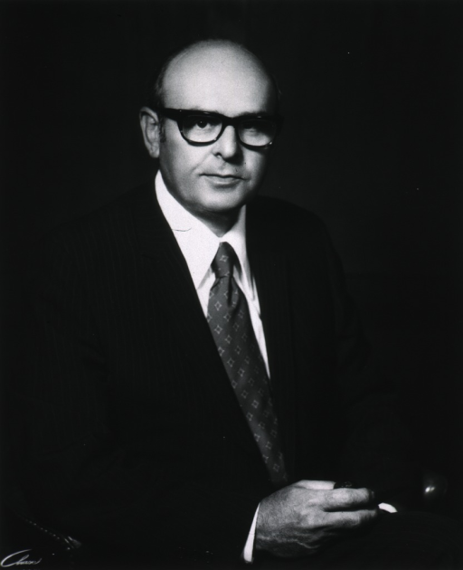 <p>Half-length, seated, right pose, full face, wearing glasses, holding pipe.</p>