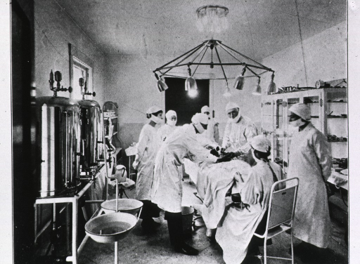 <p>Interior view of the operating room with operation in progress; two surgeons and several assistants are present; hot water tanks and other apparatus are against the wall on the left; glass enclosed shelving is against the wall on the right.</p>