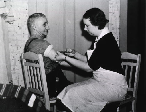 <p>A nurse gives an injection to an elderly man in his home.</p>