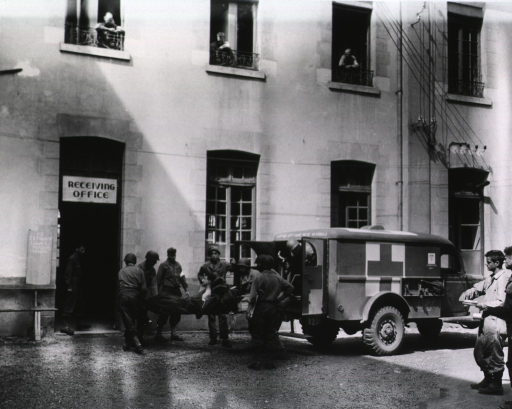 <p>A crew of servicemen carries a wounded soldier on a stretcher from the back of a U.S. army ambulance toward the doorway of a building. Above the doorway hangs a sign that reads &quot;receiving office.&quot; Other men observe from second story windows and from the courtyard in front of the hospital.</p>