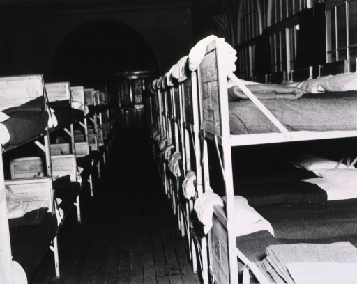 <p>Interior view of a room furnished with two rows of unoccupied bunk beds.</p>