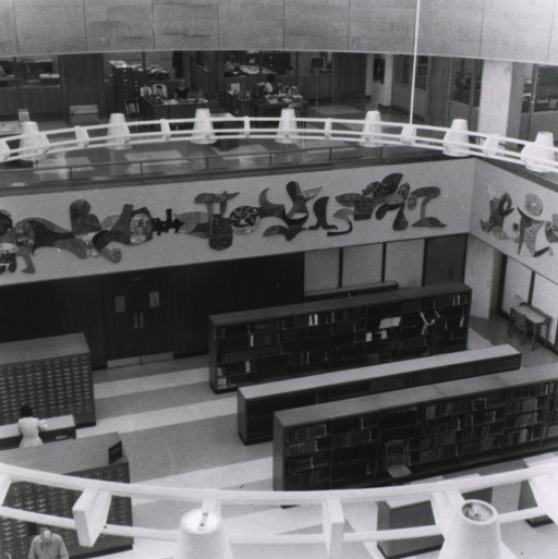 <p>View of the rotunda from the mezzanine that includes offices on the mezzanine, a partial view of the mural, some of the card catalog, and shelves of reference works.</p>