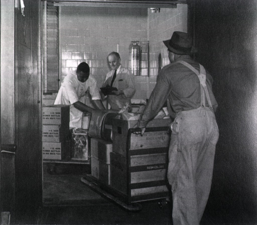 <p>A man is moving a pallet of wooden boxes into a tiled room.  On the side of the boxes it is written: return to storage room when empty.  An African American man is standing behind a pallet of boxes with specimen bottles.  A third man, holding a clip board, is standing by a fire extinquisher.</p>