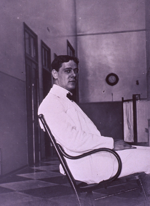 <p>Three-quarter length, seated, leaning back in chair, body in profile, face front; wearing white coat.</p>