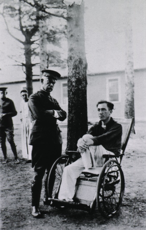 <p>Full length, standing; wearing uniform; talking to patient in wheelchair on grounds at Walter Reed Hospital.</p>