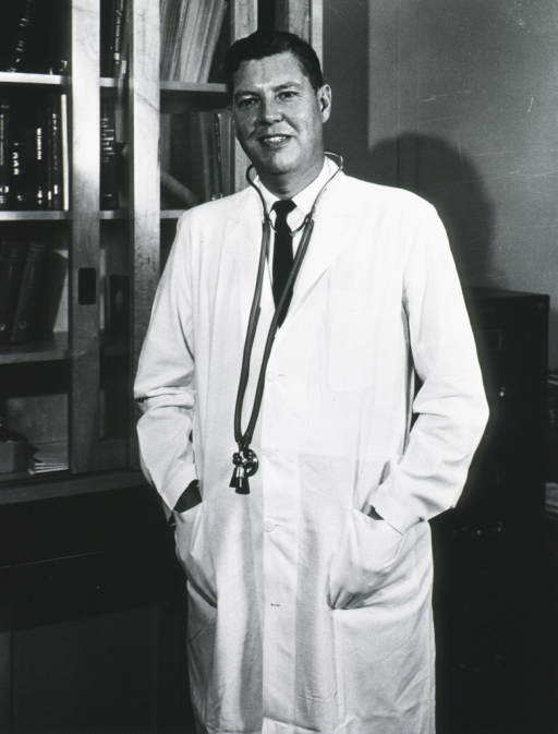 <p>Three quarter length, full face; standing in front of bookcase; wearing lab coat; stethoscope around his neck.</p>